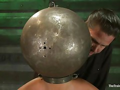 Adrianna Luna has her legs held apart by a support and her hands are encased by metal balls. Her head is encased by a metal ball as well and pumps on her nipples. She receives a sex tool on her cunt and receives the ok to cum. Then she's tied to a table and having clamps put on her cunt and tits. Freaky!